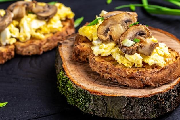 Uova strapazzate con funghi champignon su pane croccante di frumento e segale, colazione sana o brunch.
