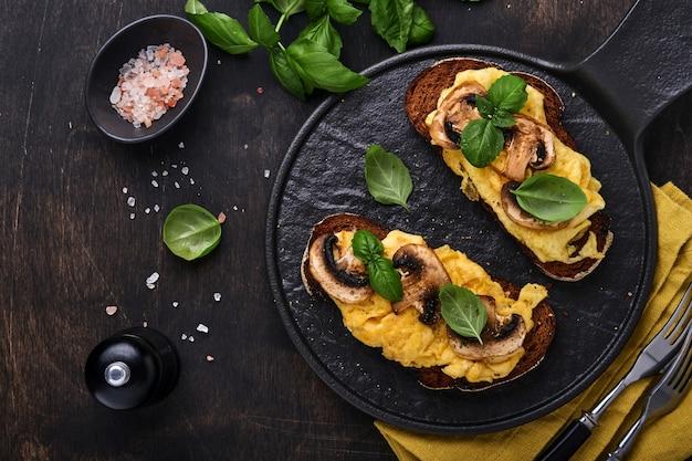 Uova strapazzate con funghi fritti e basilico su pane nero sullo sfondo della tavola. colazione fatta in casa o pasto per il brunch: uova strapazzate e panini ai funghi. vista dall'alto con copia spazio