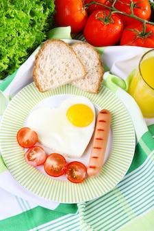 Uova strapazzate con salsiccia e verdure servite su piatto su tessuto