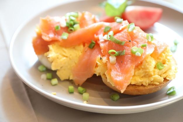 Uova strapazzate con salmone affumicato su pane tostato, cibo per la colazione
