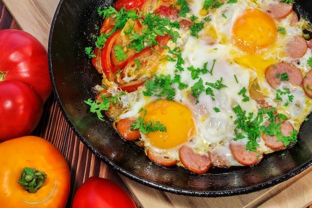 Uova strapazzate con pomodori, salsicce, peperone dolce e cosparse di prezzemolo tritato in una padella antiaderente