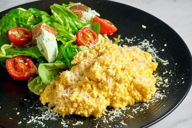 Frittata strapazzata con insalata di spinaci, ricotta e pomodorini, servita in un piatto nero su marmo