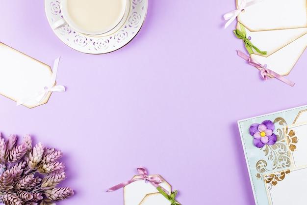 Fondo dell'album per ritagli con la decorazione, tazza di tè, fiori su fondo porpora, spazio della copia.