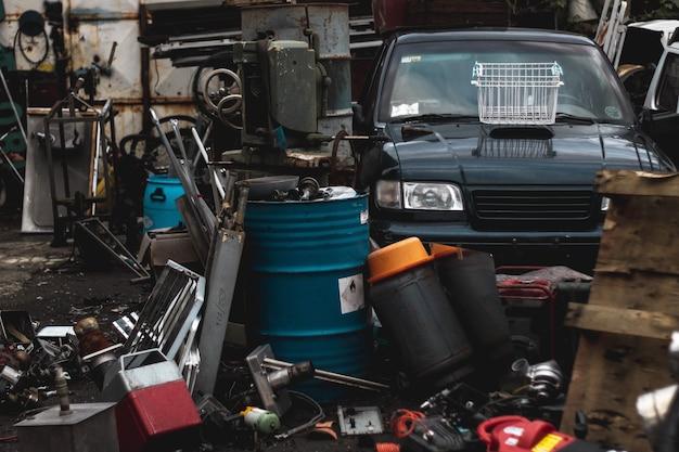 Scrapyard con un sacco di spazzatura metallica e una macchina