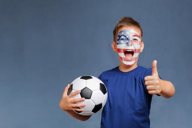 Il tifoso di football americano di grido tiene il pallone da calcio e gesticola i pollici in su
