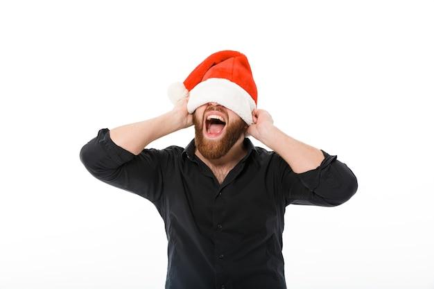 Uomo barbuto di grido in camicia che tiene il cappello di natale sugli occhi