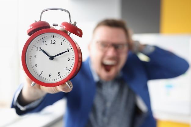 L'uomo d'affari urlante tiene la sveglia rossa nel concetto di gestione del tempo delle mani