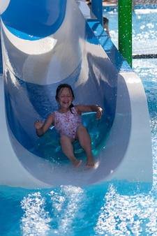 Una ragazza urlante in costume da bagno rosa cavalca su un cerchio gonfiabile da uno scivolo d'acqua in un parco acquatico