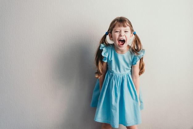 Bambina di grido in vestito blu sulla parete neutrale