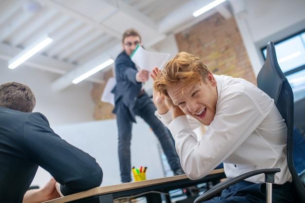 Capo maschio di grido con documenti in piedi sulla scrivania e dipendente dai capelli rossi spaventato