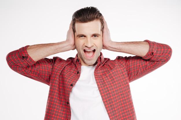 Uomo urlando che copre le sue orecchie