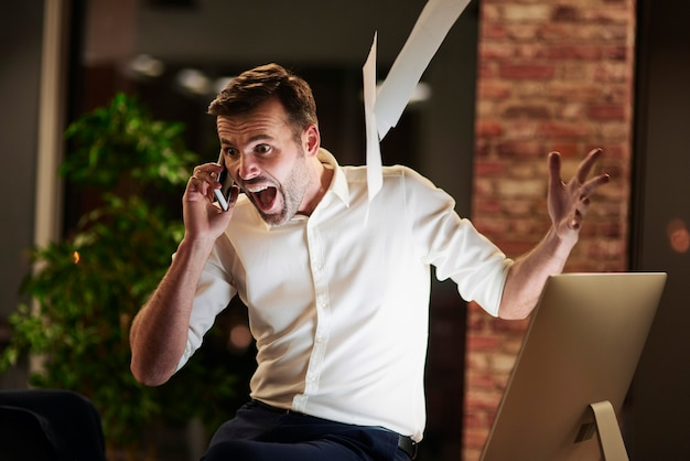 Uomo urlante che parla al cellulare in ufficio