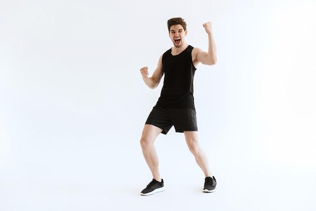 Urlando giovane sportivo positivo che corre e fa il gesto del vincitore.