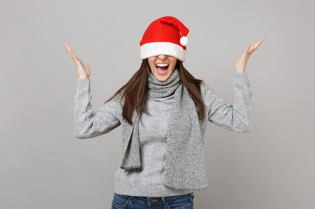 Urlando santa ragazza in maglione grigio sciarpa che copre gli occhi con il cappello di natale diffondendo le mani isolate su sfondo grigio muro. felice anno nuovo 2019 celebrazione festa concetto. mock up copia spazio.