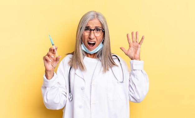 Urlando con le mani in alto, sentendosi furioso, frustrato, stressato e turbato. medico e concetto di vaccino