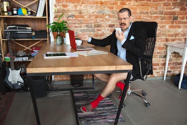 Urlando. giovane senza pantaloni ma in giacca che lavora su un computer, laptop. ufficio remoto durante il coronavirus, divertente e comodo in mutande. isolamento, quarantena, umorismo, concetto di business.