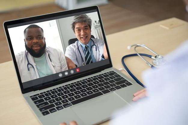 Visualizzazione dell'applicazione sullo schermo di un medico anziano asiatico e afroamericano indossa uno stetoscopio in camice bianco sul collo e videoconferenza per la discussione e la condivisione come curare il virus. concetto di telemedicina