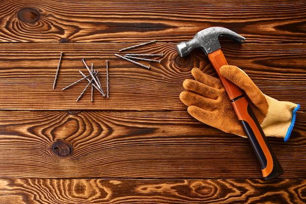 Avvitare chiodi, martello e guanto sulla tavola di legno. strumento professionale, attrezzatura da falegname, elementi di fissaggio, strumenti di fissaggio e avvitamento