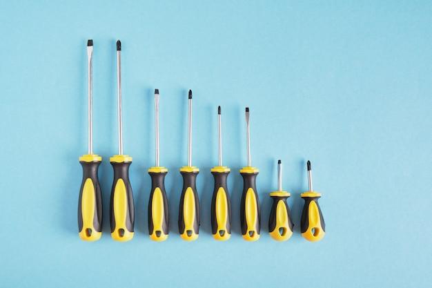 Cacciavite impostato su uno sfondo blu vista dall'alto copia spazio molti cacciaviti con impugnature nere e gialle