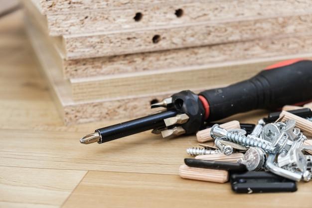 Cacciavite con ugelli rimovibili su parti di mobili dell'armadio in truciolare laminato
