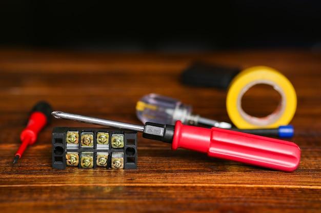 Cacciavite, nastro isolante giallo, connettore del cavo, morsettiere. set da elettricista. foto di alta qualità