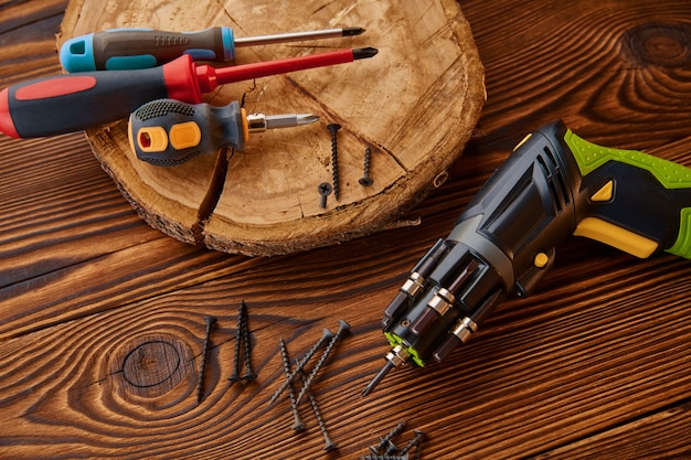 Cacciaviti e viti autofilettanti sul moncone, primo piano, tavolo in legno. strumento professionale, attrezzatura da falegname, utensili per la lavorazione del legno