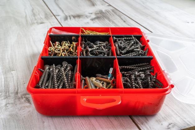 Viti, bulloni, dadi e altri oggetti da falegname in una cassetta degli attrezzi di plastica (organizzatore dell'hardware). foto d'archivio.