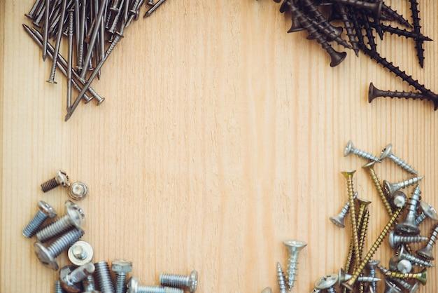 Le viti si avvicinano ai chiodi e ai bulloni sulla tavola di legno