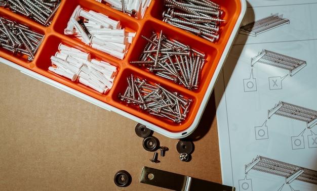 Viti e tassello in scatola di plastica arancione vista dall'alto della cassetta degli attrezzi su sfondo marrone con istruzioni di montaggio dello stendino per stoviglie