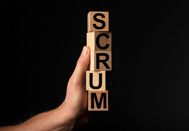 Parola di mischia su blocchi di cubo di legno in mano maschile su sfondo nero concetto di metodi di gestione