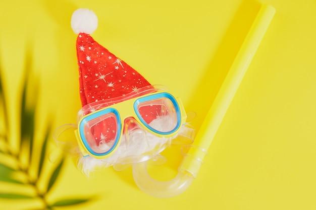 Set per immersioni subacquee, cappello di babbo natale e foglia di palma su sfondo giallo, vacanze di natale sulla spiaggia