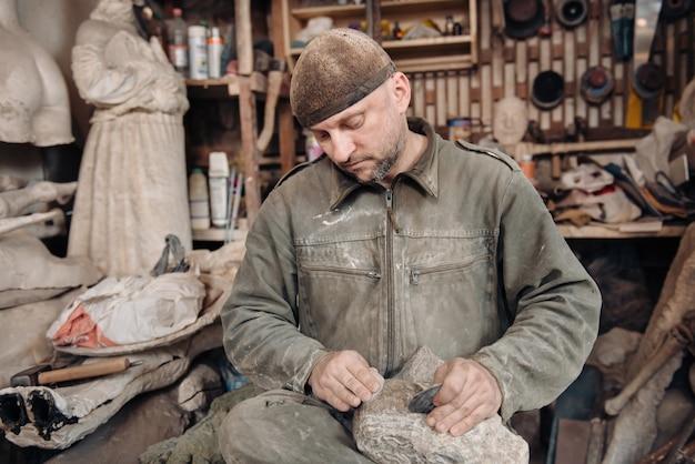 Uomo scultore che lavora nel suo laboratorio