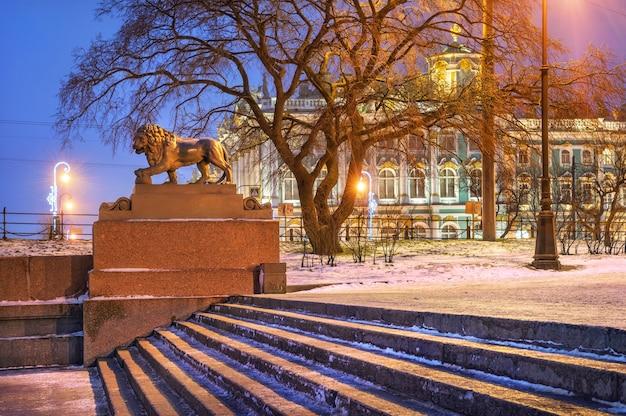 Scultura di un leone sull'argine della neva a san pietroburgo e l'eremo attraverso i rami in una mattina d'inverno