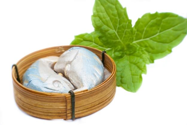 Scultura pesce sgombro nel cesto di bambù su sfondo bianco