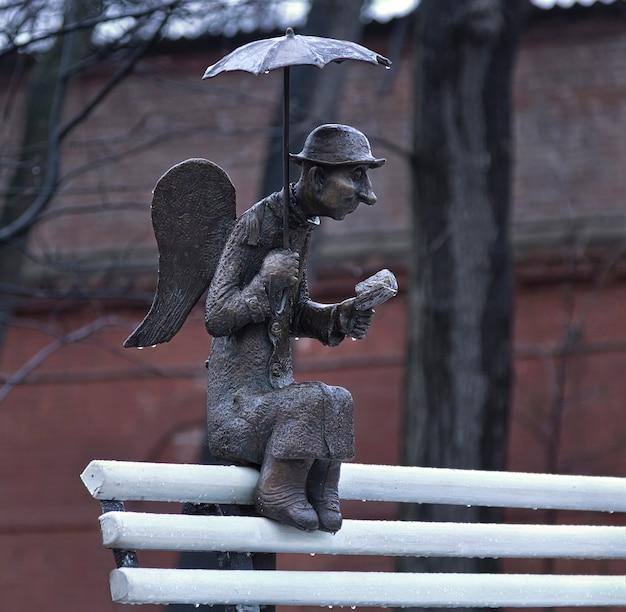 Scultura di un angelo di san pietroburgo sotto un ombrello con un libro su una panchina bianca a san pietroburgo