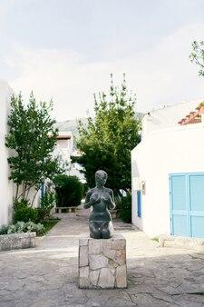 Scultura di una ragazza nuda seduta su un piedistallo davanti agli edifici