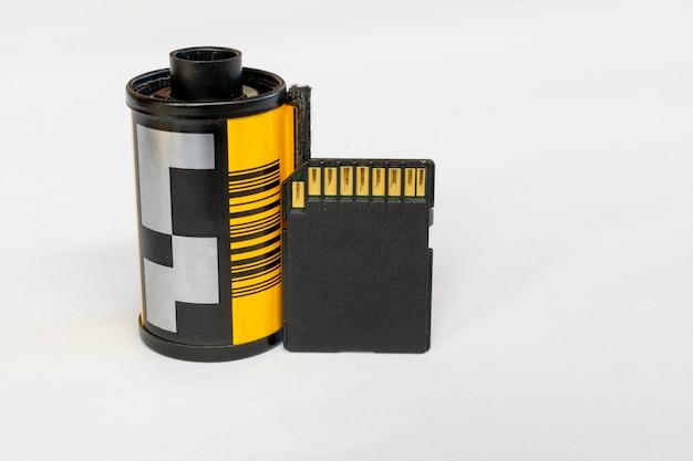 Una scheda sd per fotocamera digitale appoggiata a una vecchia pellicola da 35 mm