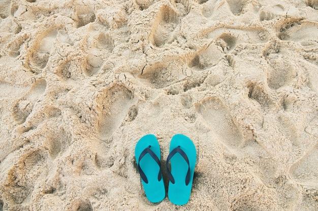 Mare sulla spiaggia impronta persone sulla sabbia e pantofola dei piedi in scarpe sandali sulla sabbia della spiaggia, concetto di vacanze di viaggio.