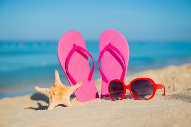 Il mare, la spiaggia, la sabbia e gli accessori da donna: infradito rosa, occhiali da sole rossi e stelle marine