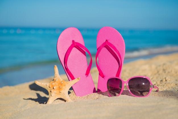 Il mare, la spiaggia, la sabbia e gli accessori donna: infradito rosa, occhiali da sole e stelle marine