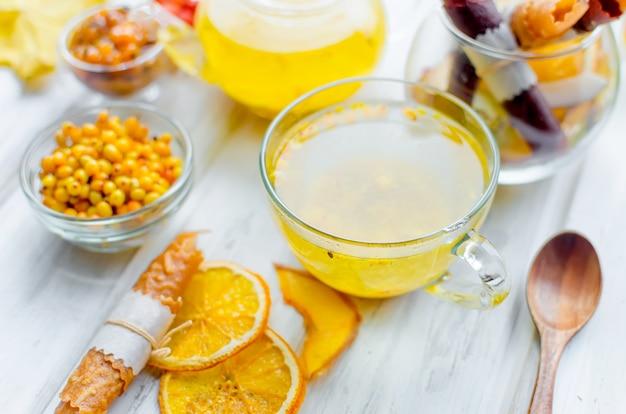 Tè all'olivello spinoso in tazza di vetro e teiera e molte varietà di pastiglie e patatine alla frutta