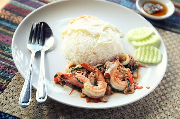 Frutti di mare con basilico e uova serviti con riso