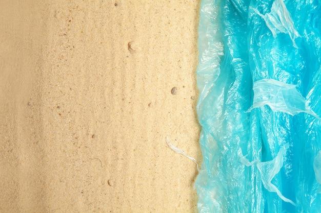 Il mare dal sacchetto di plastica va alla spiaggia di sabbia