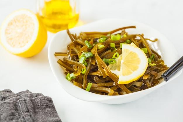 Insalata di alghe di cavolo riccio di mare con olio in una piastra bianca, sfondo bianco. concetto di cibo vegano sano.
