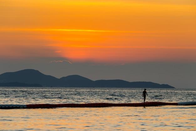 Il paesaggio del mare e un turismo femminile camminano sulla schiuma nel mare con l'ora del tramonto, pattaya thailandia