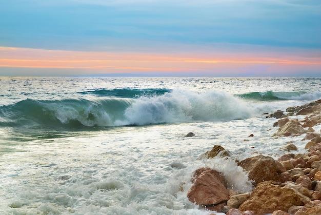 Paesaggio di mare con onde sulla spiaggia contro il tramonto