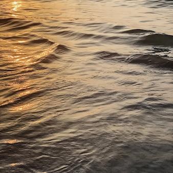 Acqua di mare o oceano con piccole onde rilassanti e riflesso del tramonto arancione colorato