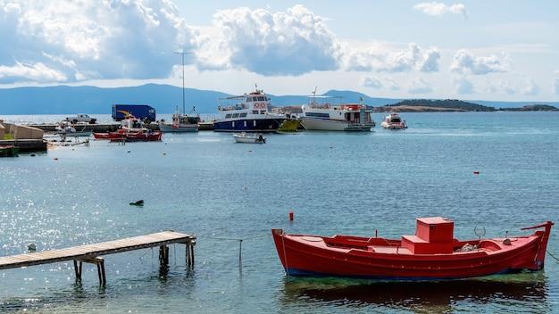 Porto marittimo, più barche ormeggiate sul mar egeo, poche auto su un molo a ouranoupolis, grecia