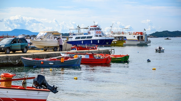 Porto marittimo, più barche ormeggiate sul mar egeo, un uomo ha agganciato una barca all'auto su un molo a ouranoupolis, grecia