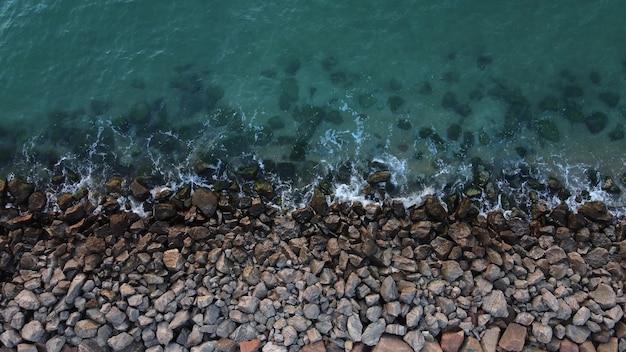 La riva del mare è ricoperta di pietre, le onde colpiscono la costa rocciosa.